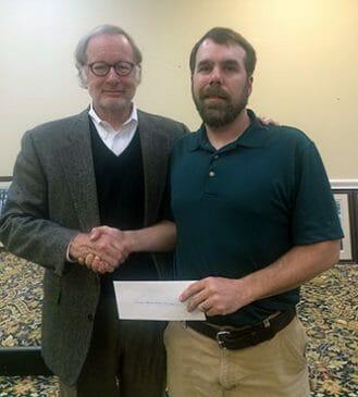 Brent Howze receives check from Bobby McKinney