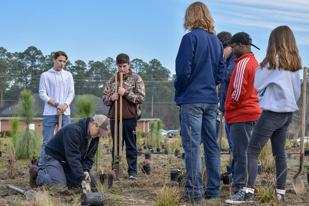 Brian Wiebler, Red Hills Outreach & Education Coordinator, demonstrates proper planting techniques to students.